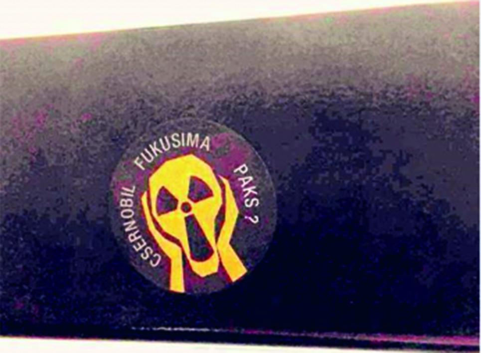 """Matrica a budapesti 28-as villamos egyik ablaküvegén. [2] A radioaktív veszélyjelzésre figyelmeztető sikoltó arc körül a """"CSERNOBIL FUKUSIMA PAKS?"""" felirat olvasható."""